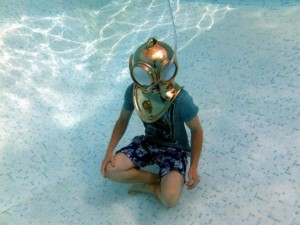 Photo of diver trying out a brass helmet